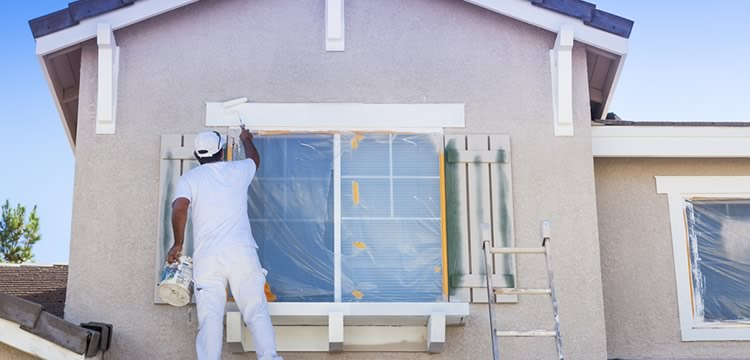 Professional Painter Painting a House Exterior