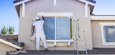 Professional painter painting window trim